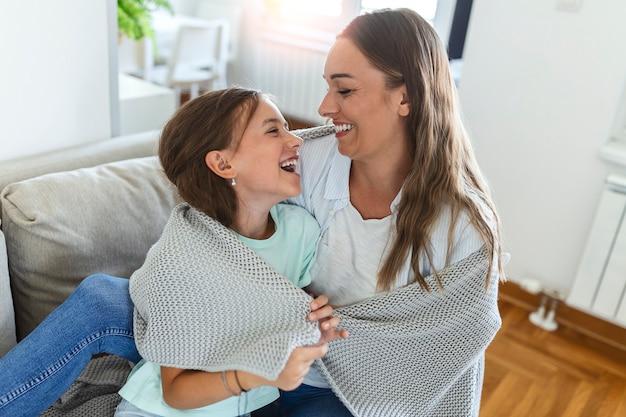 Милая девочка и ее мама наслаждаются солнечным утром. доброго времени суток дома. ребенок просыпается ото сна. семья играет под одеялом на кровати в спальне.