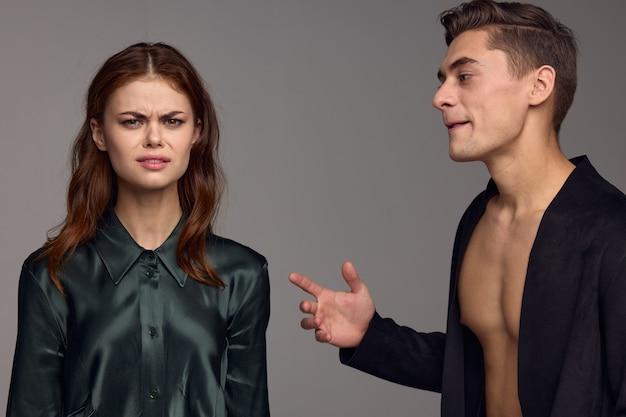 벌거 벗은 몸통에 검은 재킷을 입은 멋진 남자와 회색 벽에 멋진 여자.