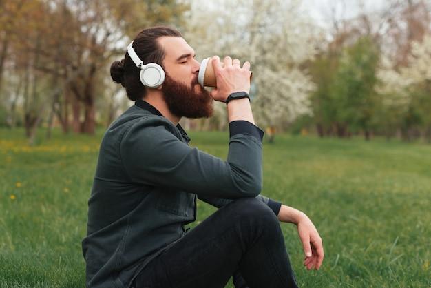 ヘッドフォンをつけてコーヒーを飲みながら自然を楽しんでいる若い男の素敵な写真