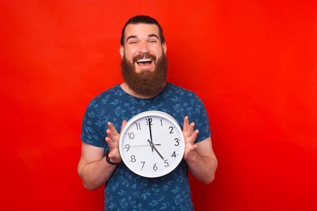 白い時計を持っている若い男の素敵な写真が赤い壁の近くのカメラに微笑んでいます