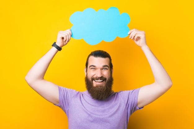 Красивое фото молодого человека с бородой, держащего облачный речевой пузырь, смотрящего в камеру