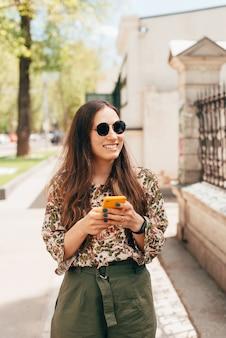 Симпатичная фотография молодой счастливой женщины, идущей возле здания и болтающей с кем-то по телефону