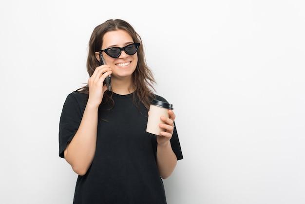 サングラスをかけて笑っている電話で話している間、彼女の熱い飲み物を飲んでいる若い女性の素敵な写真