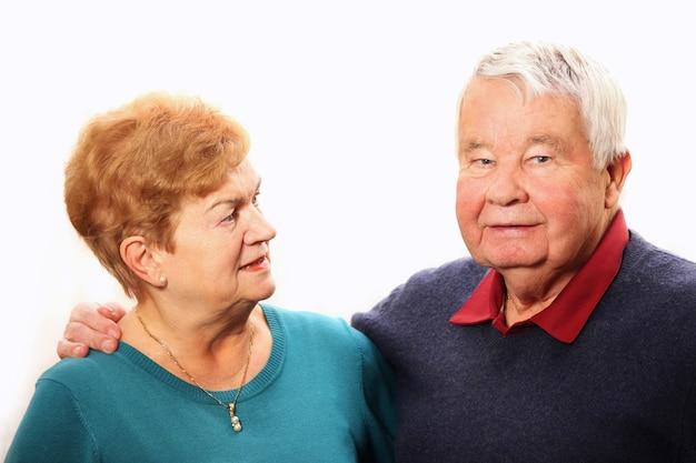 Милая пара старших разговаривает на белом фоне