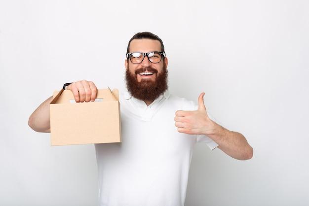 좋은 젊은 수염 배달원은 음식과 함께 상자를 들고 웃고있는 카메라를보고 엄지 손가락을 보이고있다