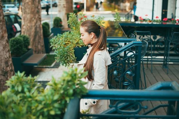 멋진 젊은 아가씨가 낮에 도시의 외부 카페에서 나가고 있습니다.
