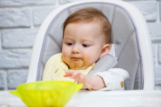 Девятимесячный улыбающийся ребенок сидит за белым столом в стульчике для кормления и ест ложкой из миски. мама кормит малыша с ложечки. размытый фон. здоровое питание для детей. детское питание.