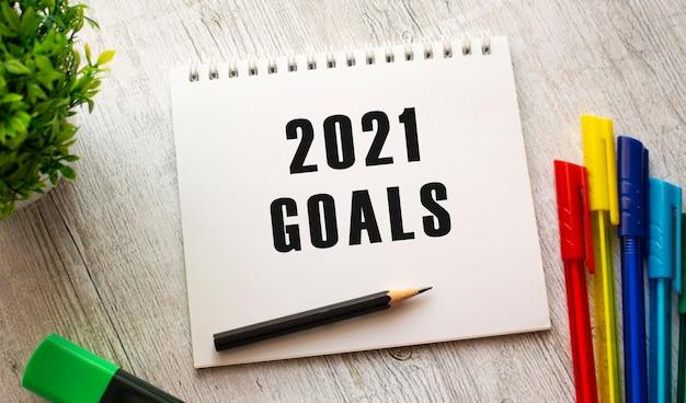 Блокнот на пружине с текстом цели 2021 на белом листе лежит на деревянном столе с цветными ручками.