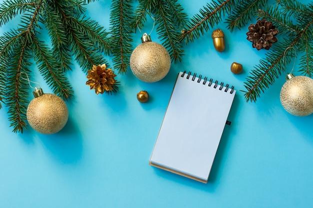 가문비나무 가지, 원뿔, 황금색 공, 견과류가 파란색 배경에 있는 노트북 페이지. 평면도. 평지. 모형.