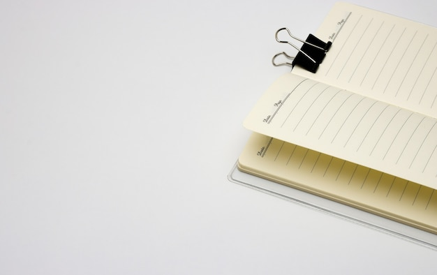 コピースペースのある白い背景にバインダークリップが付いたノートブック