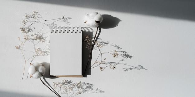 빈 페이지가 열려 있는 노트북은 마른 식물로 둘러싸인 흰색 테이블에 놓여 있습니다
