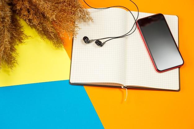 컬러 배경에 펜으로 녹음할 수 있는 깨끗한 흰색 시트가 있는 노트북, 전화기, 헤드폰, 근처에 구겨진 마른 나뭇가지. 기록, 보고, 메시지, 편지. 텍스트를 위한 장소