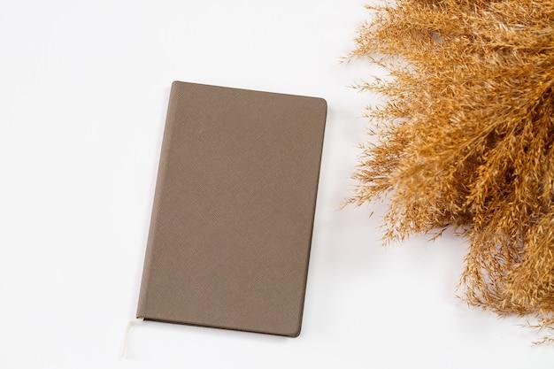 Блокнот с чистыми белыми листами для письма ручкой на белом фоне, рядом смятые сухие ветки. запись, отчет, сообщение, письмо. место для текста