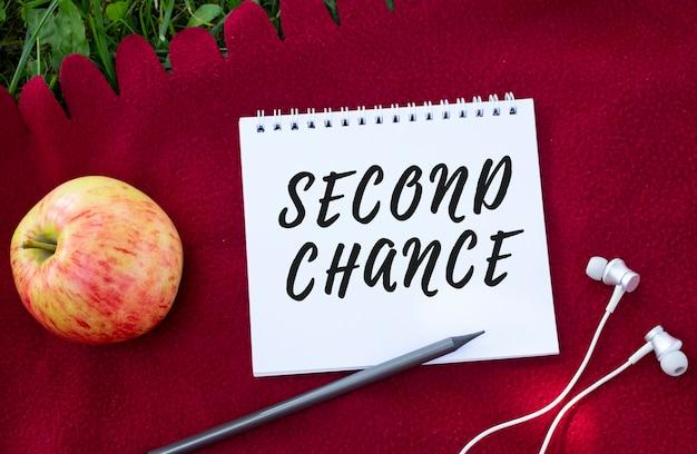 Second chance라는 글자가 있는 노트북. 근처에는 헤드폰과 사과가 있습니다. 붉은 격자 무늬와 푸른 잔디.