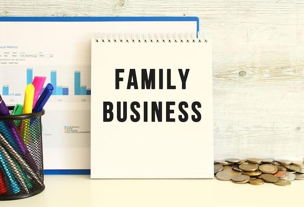Family businessというテキストが書かれたノートブックが、財務チャートの入ったフォルダーとともに壁にもたれかかっています。近くの文房具とコイン。ビジネスコンセプト。