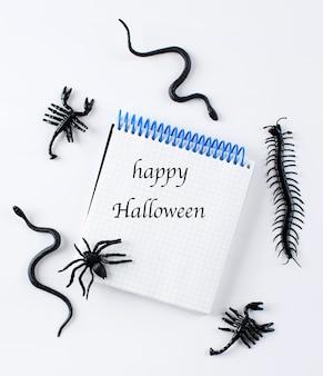 Блокнот с текстом счастливого хэллоуина в окружении фигур пауков-змей на белом фоне ...