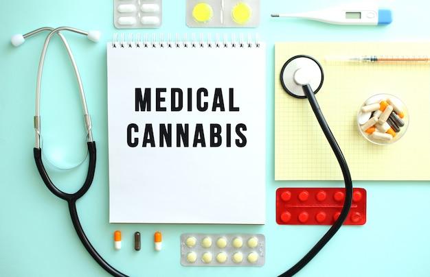 Medical cannabis라는 텍스트가 있는 노트북은 알약, 청진기, 노란색 노트북 사이에 깔끔하게 접혀 있습니다.