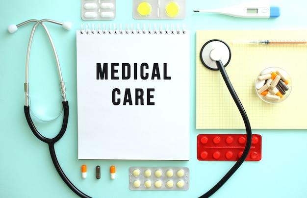 Medical care라는 문구가 적힌 공책이 알약, 청진기, 노란색 공책 사이에 가지런히 접혀 있습니다.