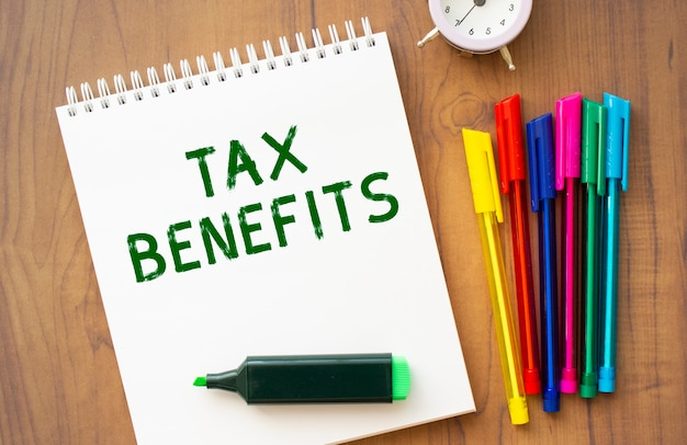 흰색 시트에 tax benefits 텍스트가있는 노트북은 컬러 펜이 달린 갈색 나무 테이블에 놓여 있습니다. 비즈니스 개념.