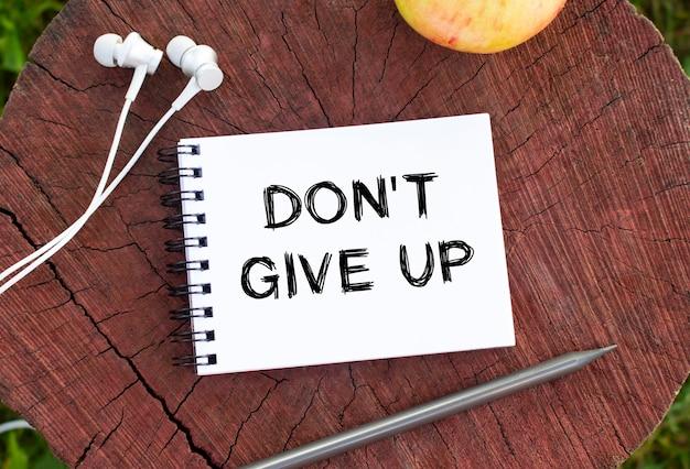 메모장, 헤드폰, 연필, 사과가 나무 그루터기에 놓여 있습니다. 노트북 페이지의 텍스트는 dont give up입니다.