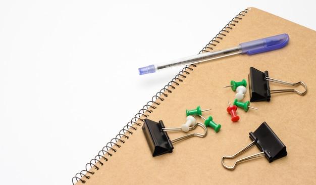 使用済みのペン、黒いバインダークリップ、コピースペースのある白い背景の画鋲が付いたメモ帳