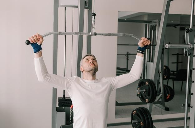 초보 보디 빌더는 시뮬레이터에서 견인 운동을 수행합니다. 체육관에서 집중 수업