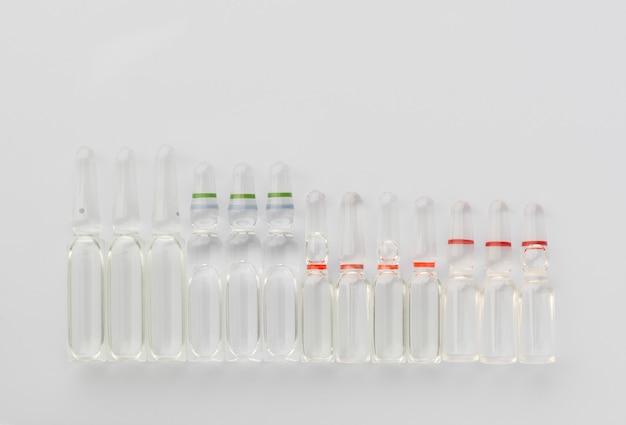 白い背景に注射用の液体の医療アンプルの数。上からの眺め