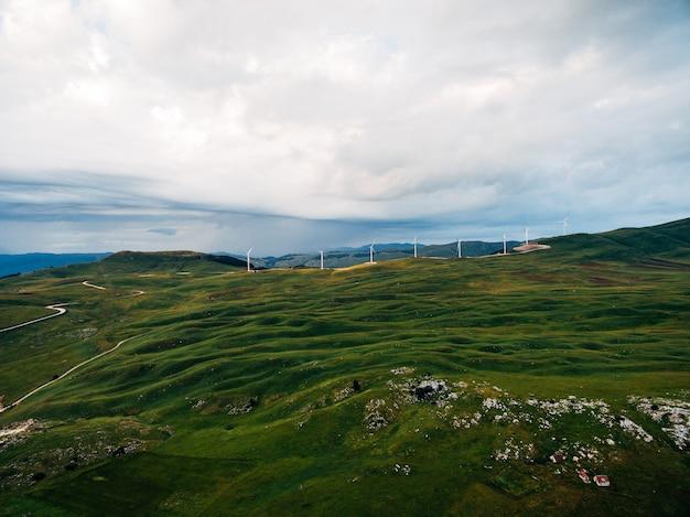 흐린 비오는 하늘을 배경으로 몬테네그로 산맥의 푸른 언덕에 많은 풍력 터빈
