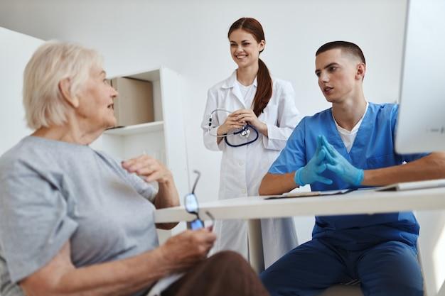 병원에서 노인 여성 환자와 이야기하는 간호사와 의사