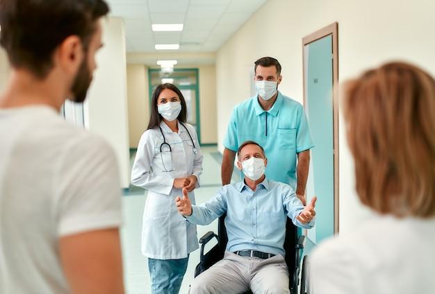 코로나 19 유행병 예방을 위해 수술 용 마스크를 쓰고있는 간호사와 젊은 의사가 가족이 방문한 병원에서 휠체어를 탄 성숙한 남성 환자를 돌보고 있습니다.