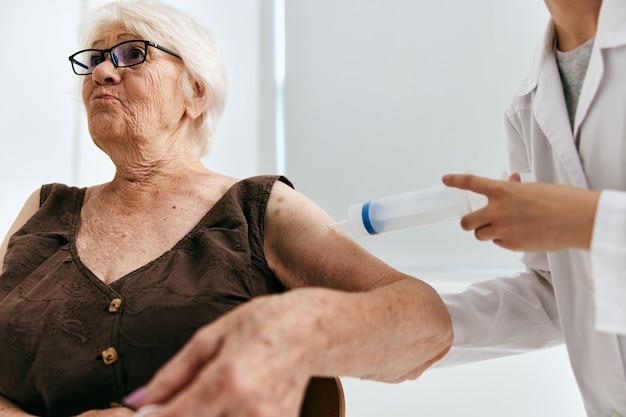 주사기 백신 여권으로 노인 여성에게 주사를주는 간호사
