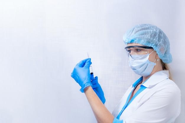 マスクと眼鏡をかけた看護師が、コピースペースのある明るい背景に注射器を持ち、感染症の予防接種を行います。