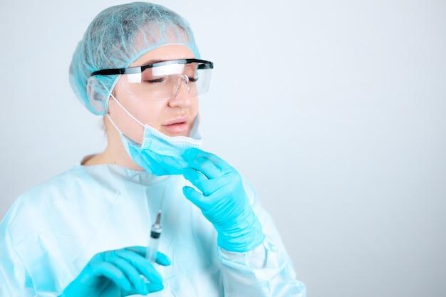 Медсестра в медицинском халате, маске и защитных перчатках с прозрачными очками на лице снимает маску, чтобы дышать воздухом.