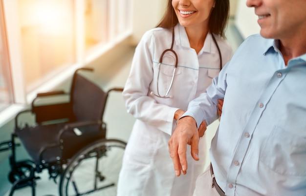 의료 복을 입은 간호사가 휠체어를 탄 성숙한 장애 환자가 다시 걷는 법을 배우도록 도와줍니다. 클리닉에서 장애인의 재활.