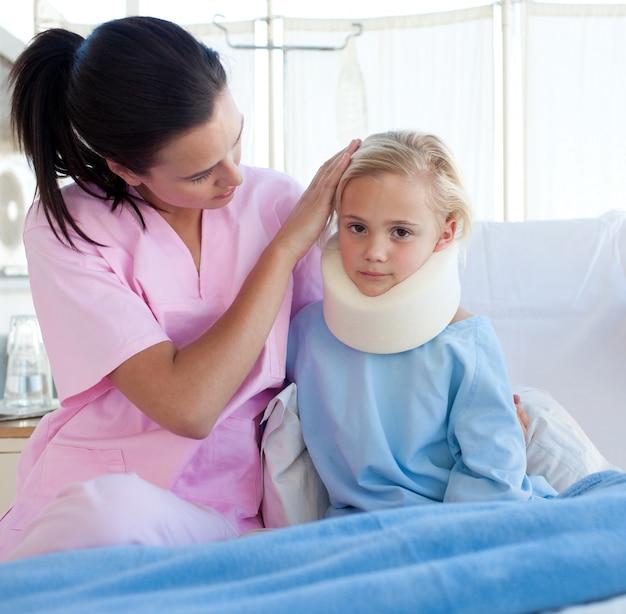 首のブレースを持つ怒った女の子を看護している看護婦