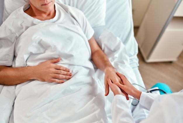한 간호사가 성숙한 남성 환자 근처에 앉아 손을 잡고 현대 병원 병동에서 그녀의 보살핌과 지원을 보여줍니다.