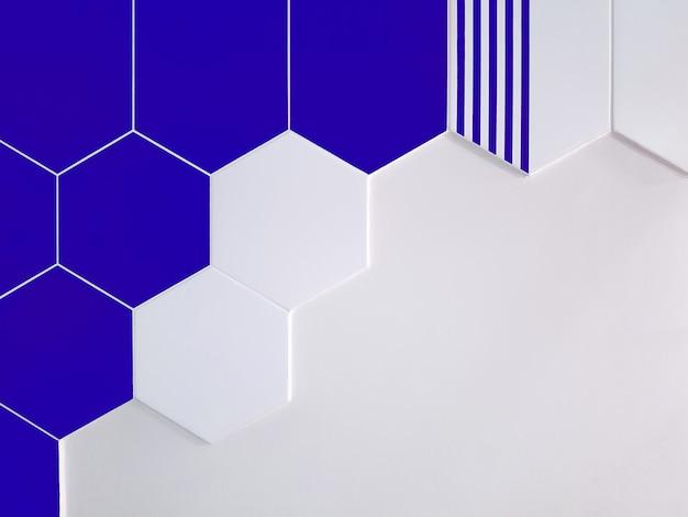 Яркая сине-белая керамическая плитка в форме шестиугольника, который частично покрывает белую стену. концепция текстуры,