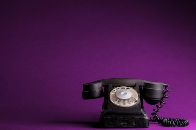 プラスチックピンクの背景に古い電話