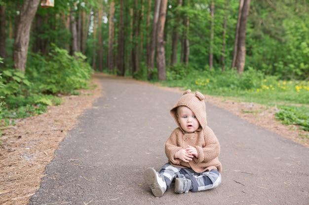 春の公園で屋外に座っている1歳の男の子緑の中を歩くかわいい幼児