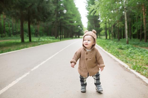Годовалый мальчик делает первые шаги на свежем воздухе в весеннем парке