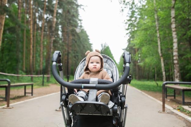 春の公園で屋外で彼の最初の一歩を踏み出す1歳の男の子