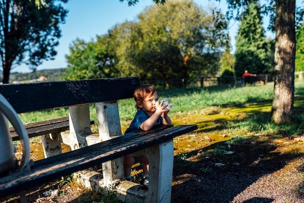 ベンチに横たわっている日没時にボトルから水を飲む1歳の赤ちゃん。赤ちゃんの水分補給自給自足