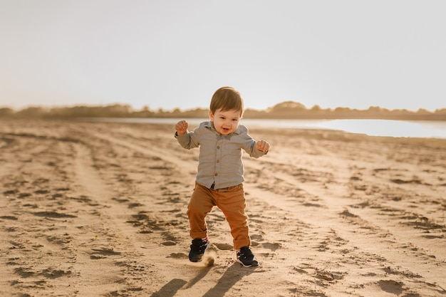 Годовалый мальчик учится ходить по песку у реки.