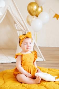Годовалая кавказская девочка в желтой одежде расстроена и плачет, студийное фото на год ребенка