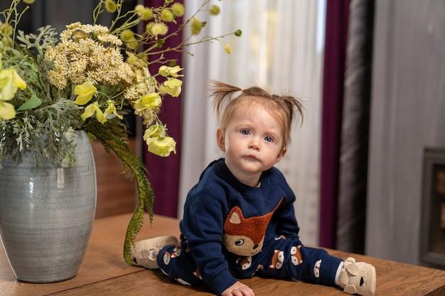 Годовалая девочка со светлыми волосами сидит на столе с большой вазой с цветами.