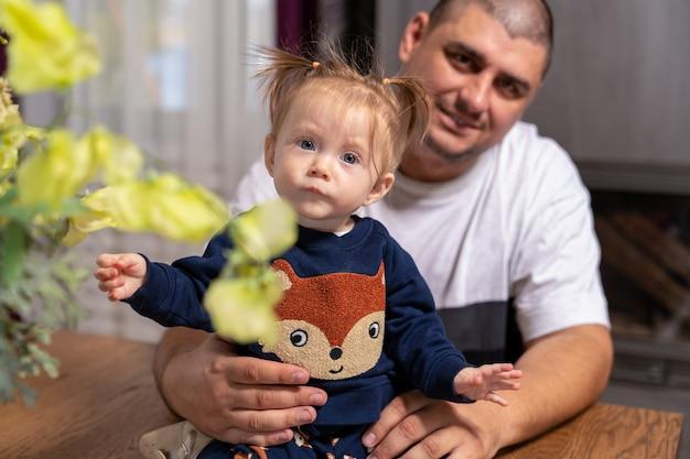 Годовалая девочка со светлыми волосами сидит на столе, а ее отец сидит рядом с ней, держась за руки