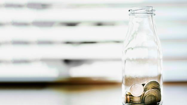Открытая бутылка с монетным стеклом перед окном