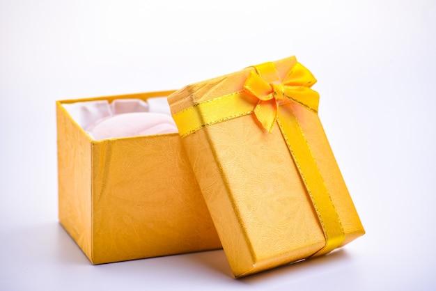白いテーブル、誕生日、クリスマス、バレンタインの日の概念に開いている金のギフトボックス。