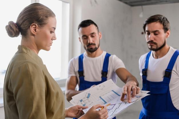 Хозяин квартиры беседует со строителями и рассматривает схему дома.