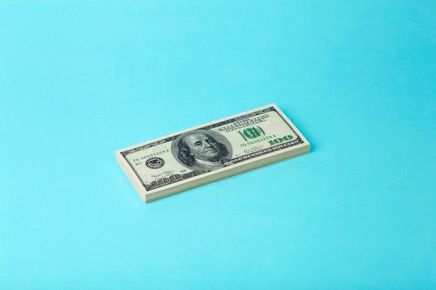 色付きの最小限の背景にドル(100ドル紙幣)のパック。お金、収入、ビジネス、賞金、利益、富の概念